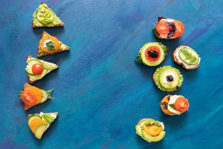 Top view oval and triangular vegetarian sandwiches on blue background. Imagens