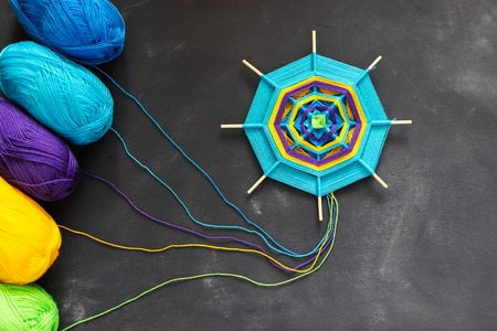 Handmade mandala of multicolor yarn threads on dark grey background. 版權商用圖片