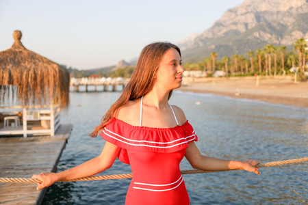 Attractive young girl in red swimsuit is standing on sea beach background.