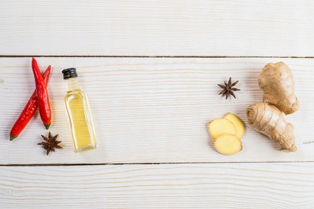 Layout of ginger and ginger oil bottle and condiments on light wooden background.