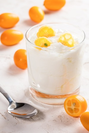 Transparent glass with white fat yogurt with kumquat slices and metal spoon on white  background.