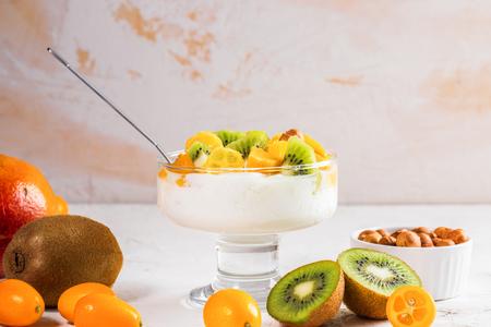 Glass bowl on stem with yogurt and fresh fruit on white background. 스톡 콘텐츠