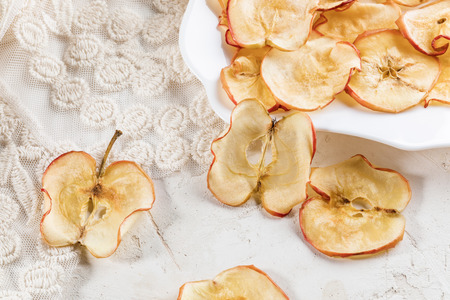 Close-up healthy natural homemade apple chips on white table and figured plate on beige lace fabric. Fruit healthy snack.