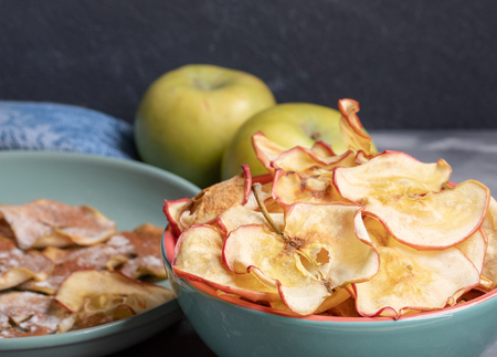 Close-up two ceramic bowls with healthy homemade apple chips and whole apples on dark grey background. Fruit healthy snack. Selective focus.