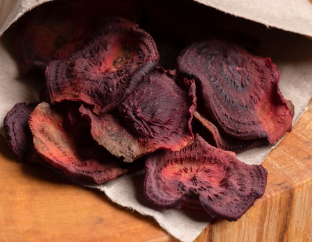 Close-up homemade beetroot chips in paper bag on wooden cut.