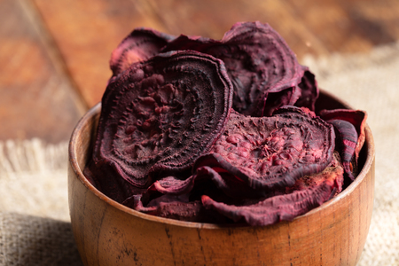 Close-up homemade healthy beetroot chips in wooden bowl.