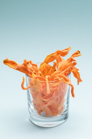 Transparent glass with homemade carrot chips on gentle blue background.