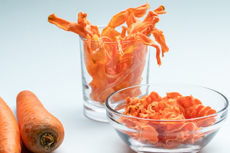 Transparent bowl and glass with orange carrot chips and whole carrots on gentle blue background. Imagens - 122283371