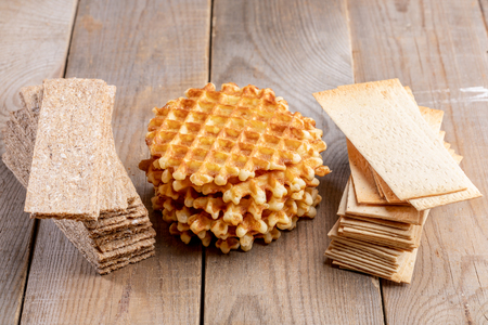 Round sweet calorie waffles and healthy grain crispbreads on  wooden table.