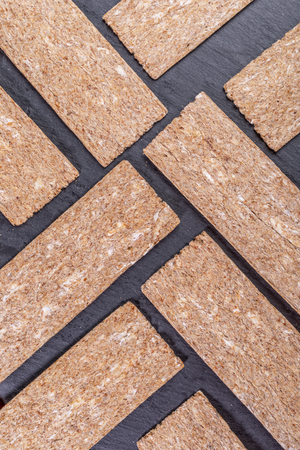 Corn crispbreads laid out in diagonal geometric pattern on  grey shale background.