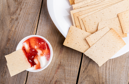 Wheat crispbreads on white plate and in bowl with sour cream and strawberry jam on wooden table. Stok Fotoğraf