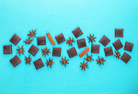 Slices of chocolate, cinnamon sticks and stars anise laid out in center of turquoise background.