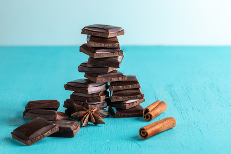 Vertical stacked slices of chocolate, cinnamon stick and star anise on  turquoise background.