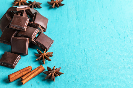Heap of slices of chocolate, cinnamon sticks and stars anise on turquoise background.