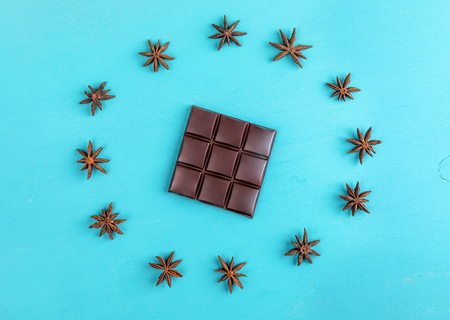 Squared bar of chocolate with stars anise laid out in circle on turquoise background.