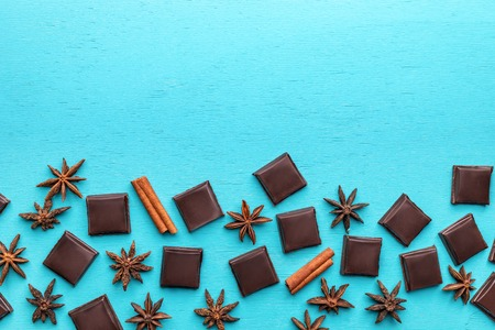 Squared slices of chocolate, cinnamon sticks and stars anise  on turquoise  background.