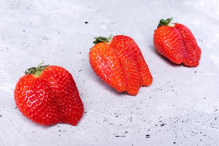 Three ugly strawberries are lying diagonally on grey concrete background. Stok Fotoğraf