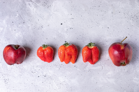 Ugly two apples and three strawberries are lying in row on grey concrete background. Zdjęcie Seryjne