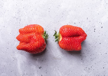 Two ugly strawberries are lying on grey concrete background.