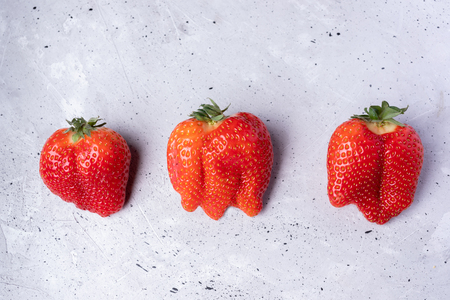 Three ugly strawberries on grey concrete background.