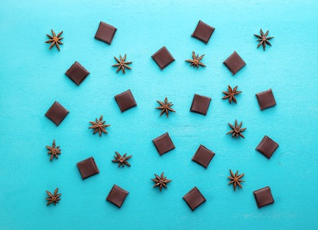 Pattern from chocolate slices and anise stars on turquoise background.