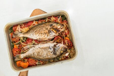 Fish, cooked on vegetable cushion in metal baking tray on white background. Zdjęcie Seryjne