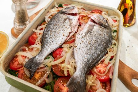 Fish, prepared for baking on vegetable cushion in metal baking tray on white table. Stock Photo