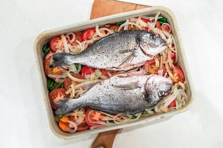 Two raw fish, prepared for baking on vegetable cushion in metal baking tray on white background.