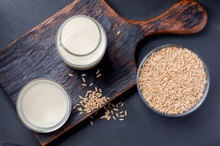 Dairy free oat milk in glass bottle and glass and oat seeds in glass bowl on wooden kitchen board on grey background. Zdjęcie Seryjne