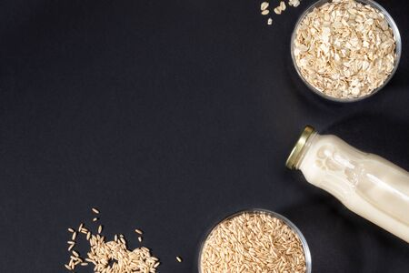 Oat seeds and flakes in glass bowls and glass bottle with oat milk on dark grey background.