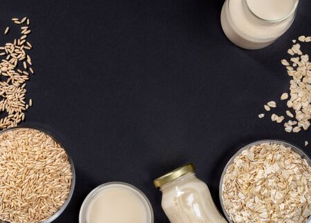 Dark grey background with frame of glass bowls with oat seeds and flakes and glass containers with  oat milk. Zdjęcie Seryjne