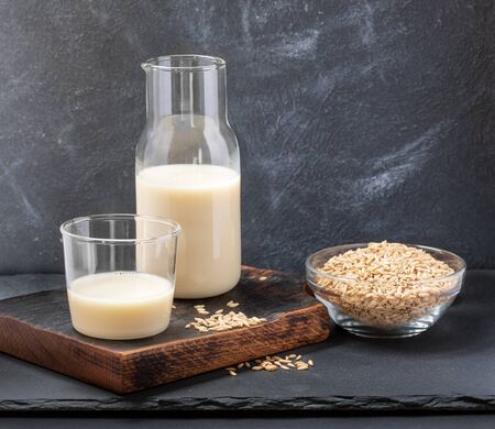 Healthy vegan dairy free oat milk in glass bottle and glass and oat seeds on glass bowl on grey background. Zdjęcie Seryjne