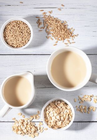Bowls with oat seeds and flakes and mugs with healthy vegan dairy free oat milk on white background. Zdjęcie Seryjne