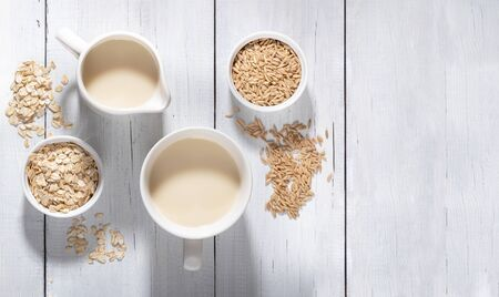 White bowls with oat seeds and flakes and  white mugs with oat milk on white wooden background.