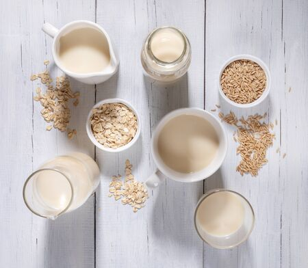 Different glass containers with oat milk, bowls with oat seeds and flakes on white wooden background.
