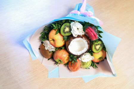 Festive packed bouquet of fruits macaroons and flowers lies on wooden table.