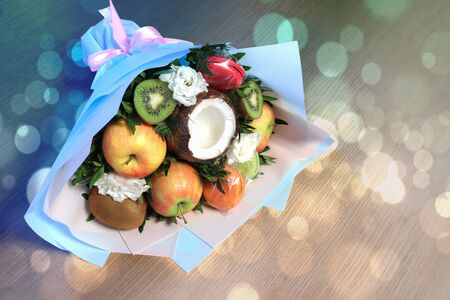 Bouquet of fruits macaroons and flowers lies on wooden table with bokeh.