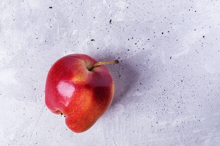 One ugly ripe red  apple on grey concrete background.