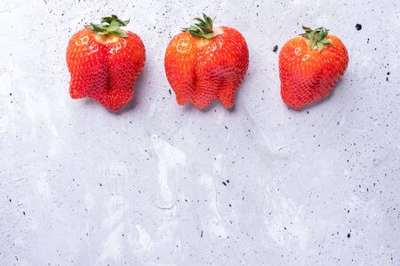 Three ugly red strawberries on grey concrete background.