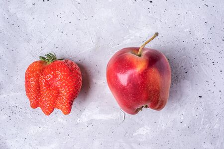 Two ugly fruits: ripe red strawberry and apple on grey concrete background. Waste zero concept. Top view.