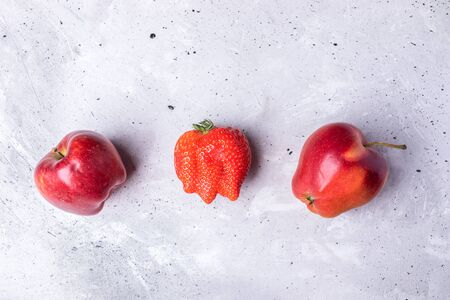 Three ugly fruits: strawberry and two apples on concrete background.