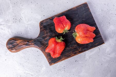 Three ugly ripe red strawberries on burned kitchen cutting board on grey concrete background. Zdjęcie Seryjne
