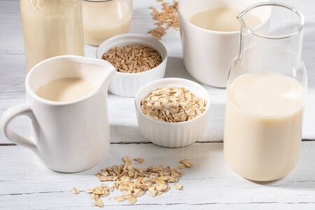 Close-up glass bottle and mug with oat milk and bowls with oat seeds and flakes on white wooden table.