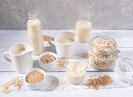 Set of different containers with oat milk, oat seeds and flakes on white wooden table on concrete background.