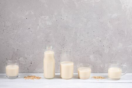 Set of glass containers with oat milk on white wooden table on concrete wall background. Zdjęcie Seryjne