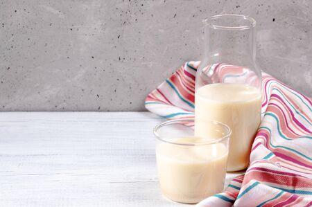 Close-up glass and bottle with oat milk and striped kitchen towel on white wooden table on concrete wall background.