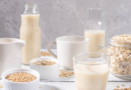 Close-up set of glass containers with oat milk, oat seeds and flakes on white table on concrete background.