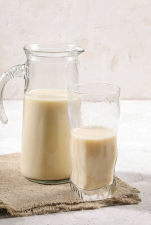Close-up decanter and glass of oat milk on burlup napkin on white background.