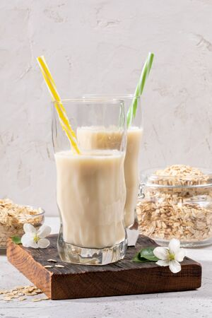 Two figured glasses with healthy oats milk on brown burned  board and jar of oaty flakes on light background.
