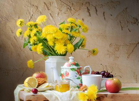 Stillleben mit Löwenzahn, Wasserkocher, Obst und Honig auf Holztisch auf altem, rissigem Hintergrund.